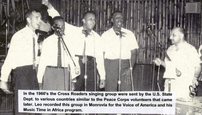 A group of singers in front of microphones, with Leo recording on the side