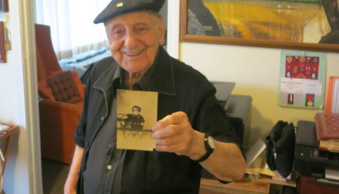 Leo Sarkisian standing in his home with a photo of himself as a child